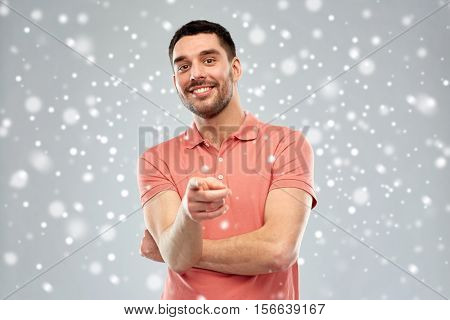 gesture, winter, christmas and people concept - happy smiling young man pointing finger to you over snow on gray background
