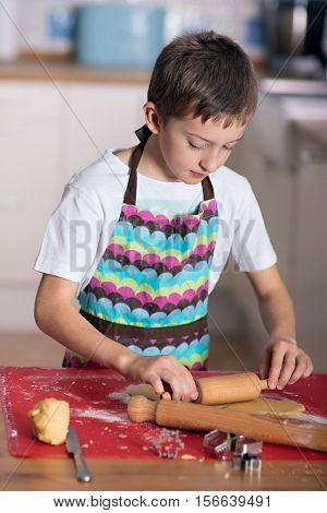 Boy cutting shapes of shortcut pastry making biscuits