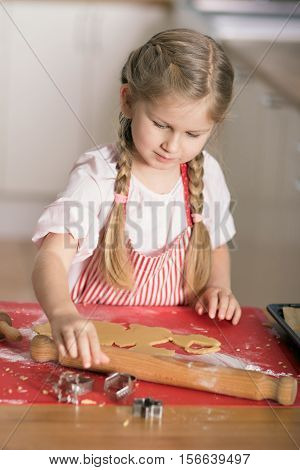 Girl cutting shapes of shortcut pastry making biscuits