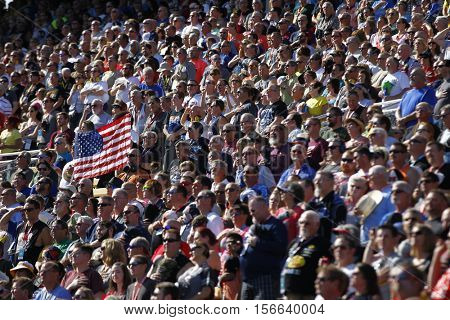 Avondale, AZ - Nov 13, 2016: Fans hold an American flag during the national anthem for  the Can-Am 500(k) at the Phoenix International Raceway in Avondale, AZ.