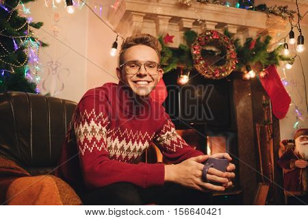 Smiling Guy On The Background Of Christmas Tree And Chimney