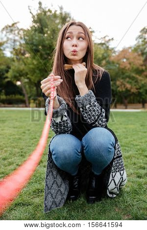 Funny playful young woman playing with dog and using bone in park