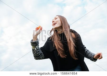 Happy attractive young woman standing and throwing ball for her dog outdoors