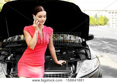 Woman with cellphone and broken car on road