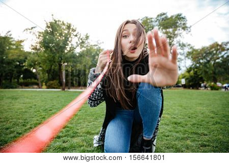 Amazed cute young woman showing stop gesture to her dog in park