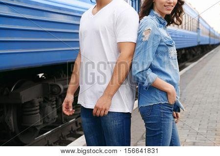 Young couple standing on railway platform near train, closeup