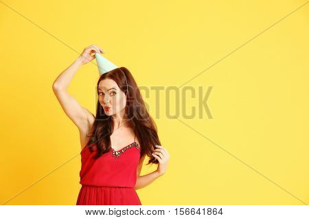 Beautiful young woman in party cap on yellow background