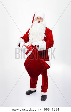 Full length of man santa claus standing and putting present box into gift sack