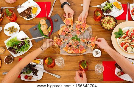 People eat pizza at festive table served for party. Friends celebrate with catering food on wooden table top view. Woman and man's hands take the pieces of italian pizza.