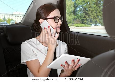 Beautiful woman with tablet and cellphone in car