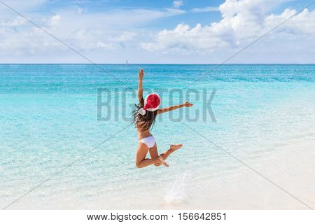 Happy Santa hat girl jumping of joy and fun on Christmas holiday travel in tropical beach destination. Winter vacation getaway woman.