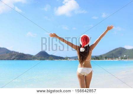 Happy Christmas holiday santa hat woman on beach vacation winning arms up in success.