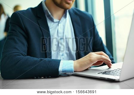 Young man working with laptop man's hands on notebook computer business person at workplace