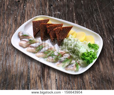 Cold snack - pieces of herring with bread and pickled onion.