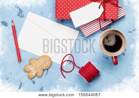 Christmas greeting card and gift boxes on stone table. Top view with copy space. Gift wrapping