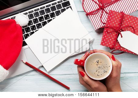 Female working on laptop and wrapping christmas gifts. Top view with copy space