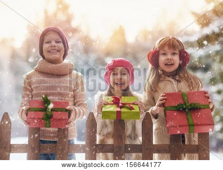 Merry Christmas and Happy Holidays! Cute children girls and boy playing on a winter walk in nature. Happy kids outdoors.