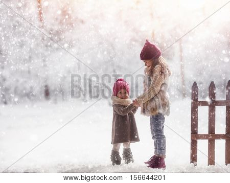 Two cute children girls playing on a winter walk in nature. Happy kids outdoors.