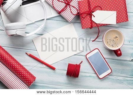 Christmas gift boxes, laptop, headphones and coffee cup on wooden background. Top view with greeting card for your text