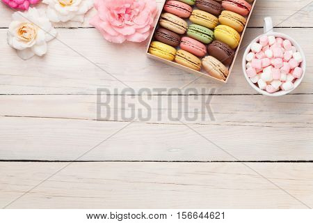 Colorful macaroons and marshmallow on wooden table. Sweet macarons in gift box. Top view with copy space for your text