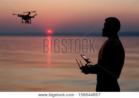 Man flying a drone near seaside at the sunset.