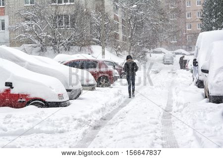 Snowstorm in Lviv Ukraine in november 13 2016. Snow-covered street and cars with a lonely pedestrian