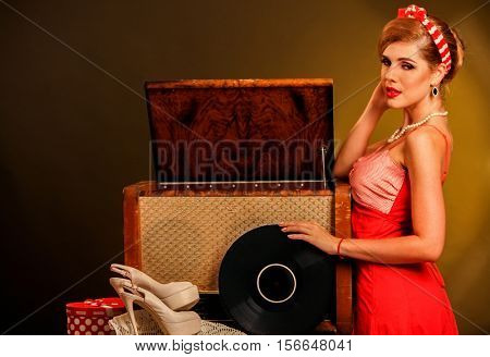 Girl in style keeps vinyl record. Pin-up retro female style. Girl pin-up style wearing red dress. Girl is going to listen to music in Christmas evening.