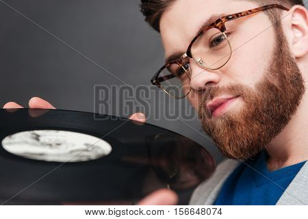 Close up man with vynil. cropped image. hipster. isolated black background