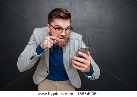 Irritated guy with phone in studio. hipster. isolated black background