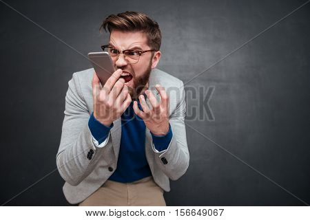 Irritated man with phone in studio. isolated black background