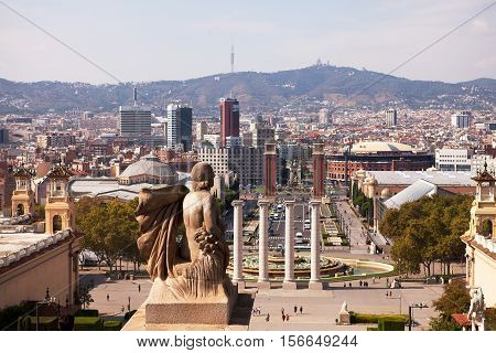 BARCELONA, SPAIN - SEP 13, 2016: A romanesque statue on the steps to the National Museum looks down toward the Placa d'Espanya and Montjuic on the horizon.