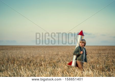 Boy with a rocket in a field