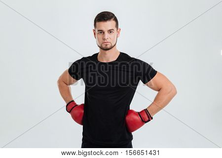 Fitness man. akimbo. isolated gray background. looking at camera