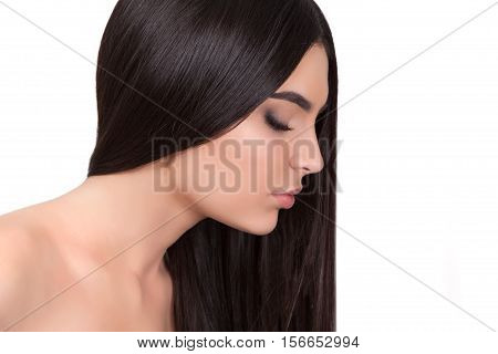 Young beautiful girl with long hair and bare shoulders looking down.
