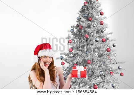 Portrait of excited woman in santa hat holding a gift against christmas background