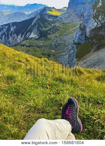 Woman with black hiking shoes resting on green meadow near Hochiss Peak with mountain view in Austria