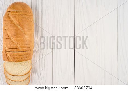Loaf of bread on white old wooden table. Top view.