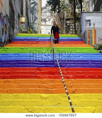 Istanbul Turkey - December 29 2013: A Turkish woman is walking in the rainbow-colored stairs on December 29 2013 in Istanbul. Rainbow-colored stairs in Istanbul. Stairs in the Cihangir and Findikli neighborhoods which attracts attention after being painte