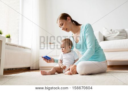 family, technology, child and parenthood concept - happy smiling young mother showing smartphone to little baby at home