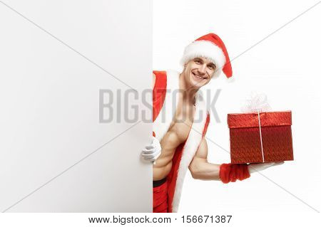 Sexy fitness Santa holding a red boxes. Muscular Santa Claus holding Christmas present in red box. Fitness Santa Happy New Year. Santa Claus with a banner sales. Christmas banner sales. Christmas sale