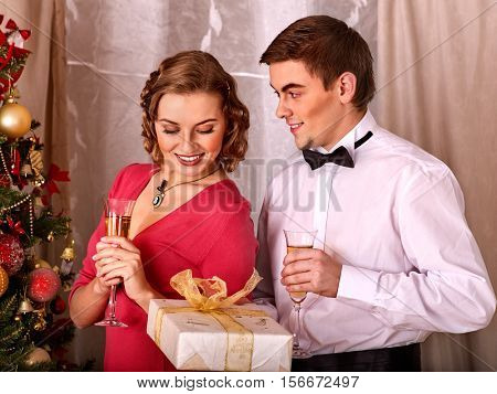 Couple on party near Christmas tree. Black and white retro. Young people decoration Christmas tree. Girl drink champagne. Man give gift box.