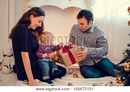 Happy family in Christmas time open gifts and presents near the Christmas tree. Happy young mother and father with their sweet baby. Merry Christmas and Happy New Year. Baby first Christmas.