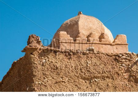 Old and not finished construction of a mosque on hill beside a road to the city Ait Ben Haddou. Dome without a tower. Bright blue sky.