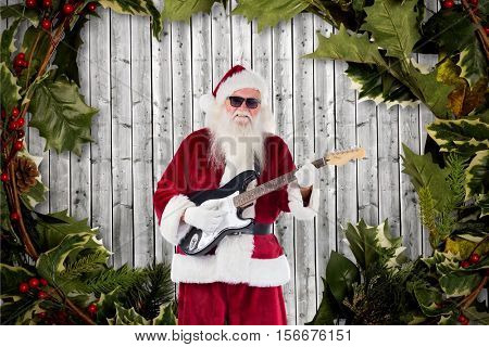 Santa claus playing guitar against digitally generated background during christmas time