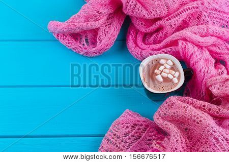 Cozy winter home background cup of hot cocoa with marshmallow old vintage books and warm knitted sweater on white painted wooden board background.