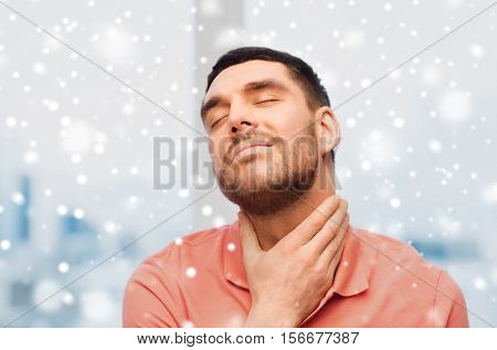 people, healthcare, winter, christmas and problem concept - unhappy man touching her neck and suffering from throat pain over snow