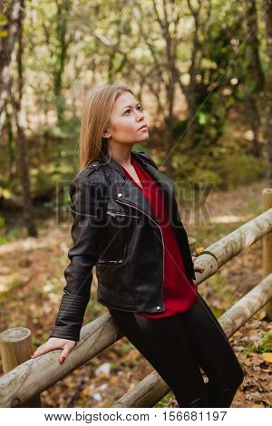 Pensive woman in a beautiful forest in autumn
