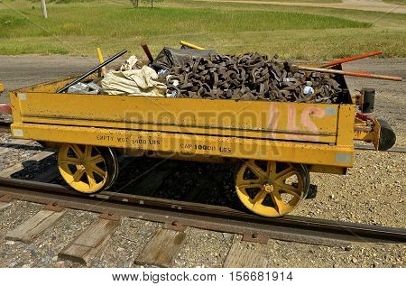 An old railroad cart full of parts for repairing train tracks is loaded for usage
