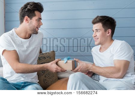 Non-traditional orientation. Cheerful young gay man smiling and giving a present to his partner while sitting together on a sofa at home.