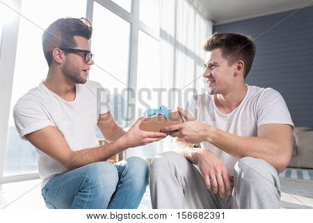 alternative relationships. Handsome young pleased man smiling and giving a present to his boyfriend while spending time together in a spacious room.